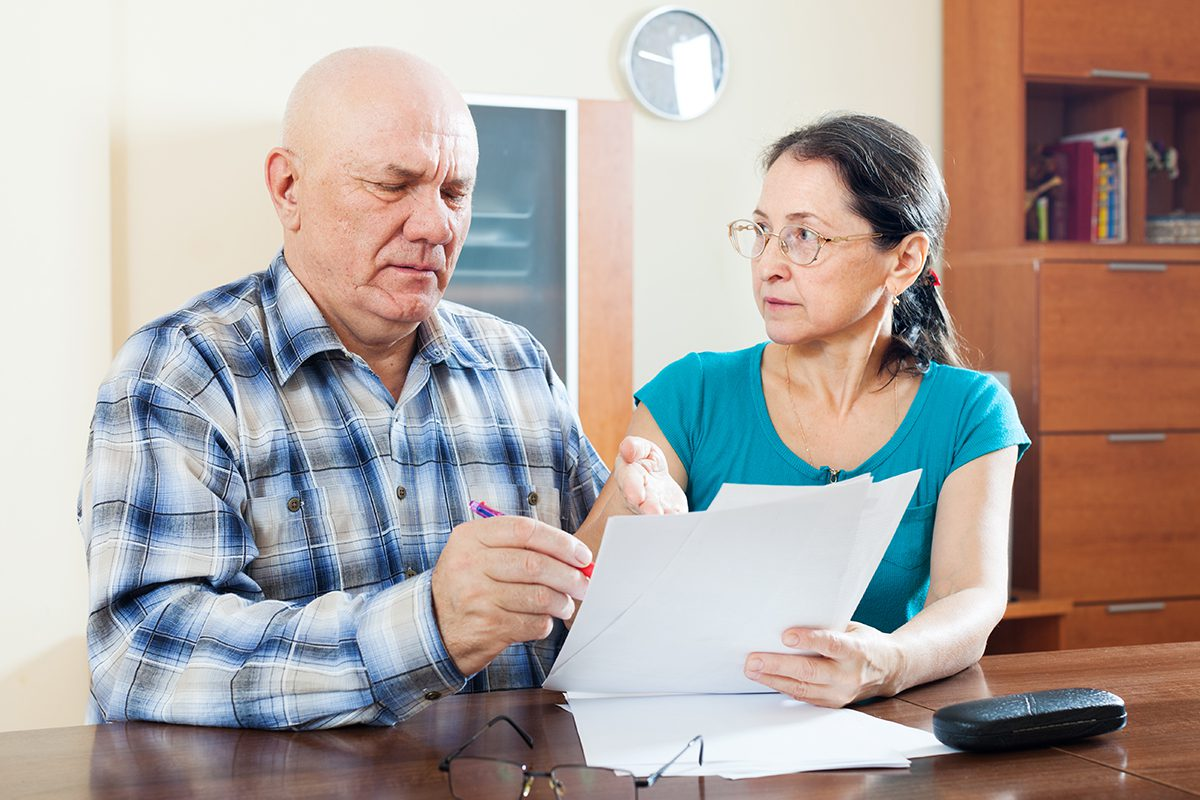 serious mature couple fills in questionnaire  at home