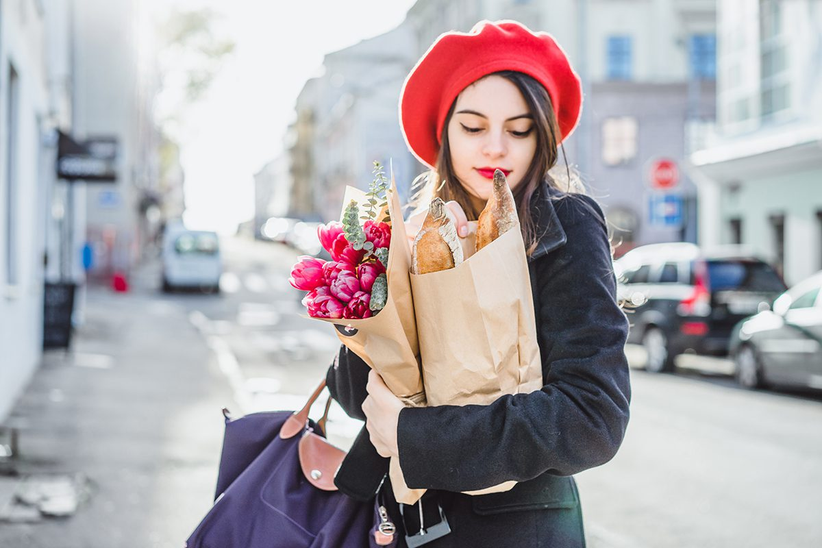 Young beautiful girl Frenchwoman brunette in a red beret and a black coat goes along the street of the European city with a bouquet of flowers and French baguettes. A happy smile and a charming look, the French style of Paris